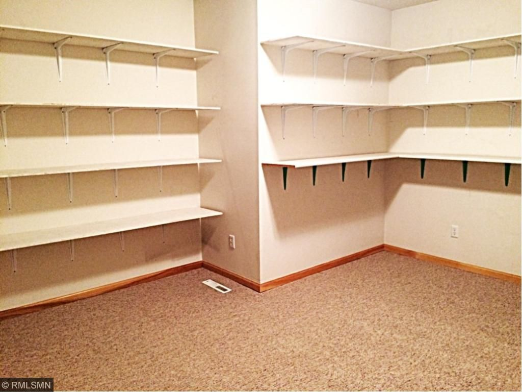 Lower level storage room with walls that are lined with shelves.   Stay organized with shelves of storage space!