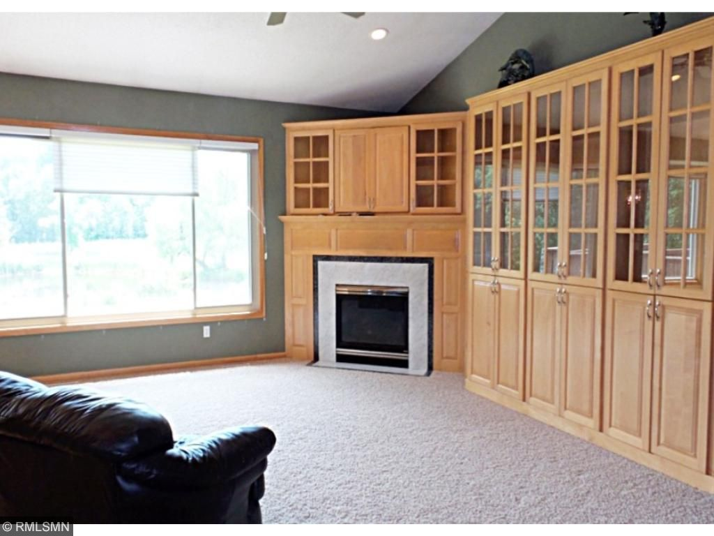 Main floor great room with picturesque views of the pond in back.  Other amenities include a gas fireplace, ceiling fan, can lights and sconces.  The highlight of the room is the wall of built-in maple cabinets with glass doors.
