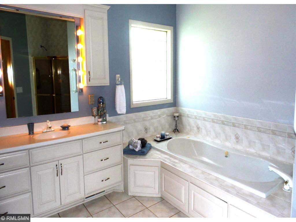 Indulge in the luxurious master bath with a whirlpool tub, glass block window and built-in TV that slides back into the cabinet when not in use.  The master bath also boasts a separate shower,  make-up mirror and linen closet.