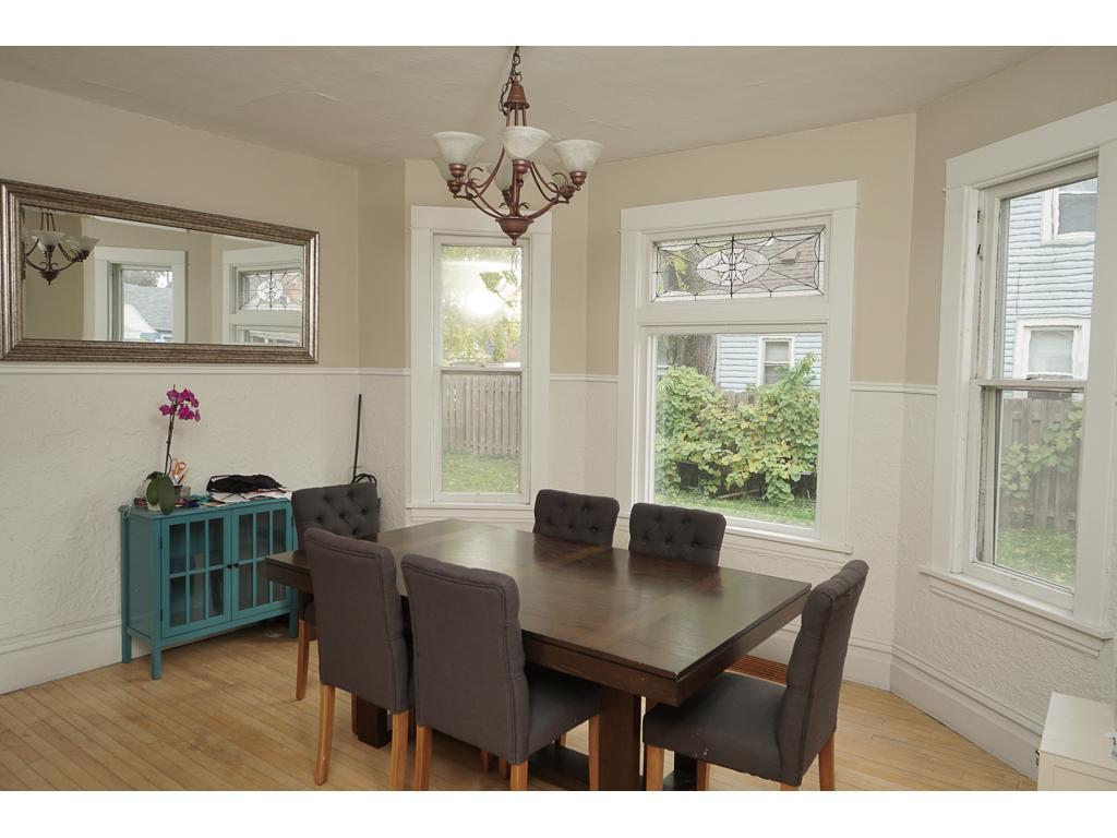 Dining with bay window, decorative glass transom window, hardwood floors.  14x13