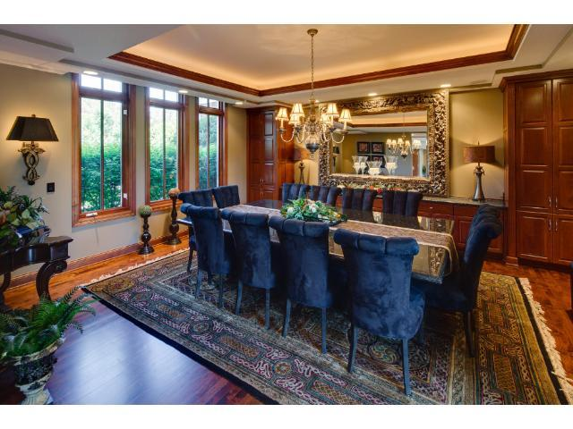 Formal dining room with custom cherry cabinetry. Coordinating granite top butler station and the one of kind granite top table that seats 12. Cherry molding and tray vault ceiling with enhanced lighting hightlight the elegance of this space