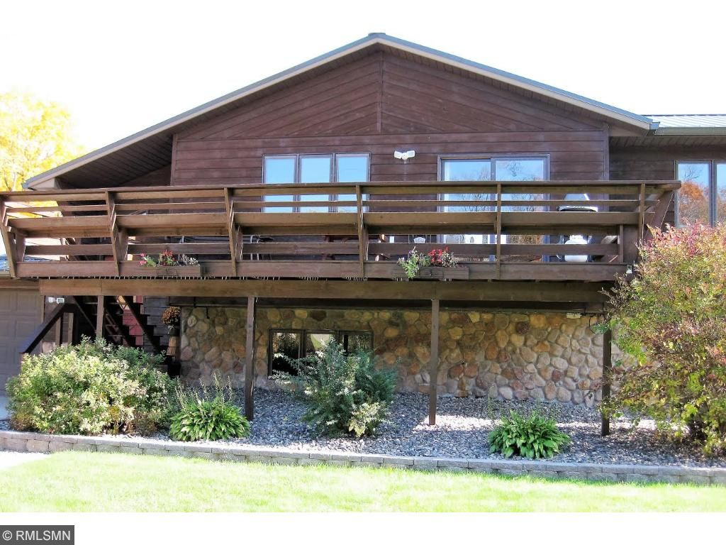 Front of home with large deck overlooking nicely landscaped front yard.