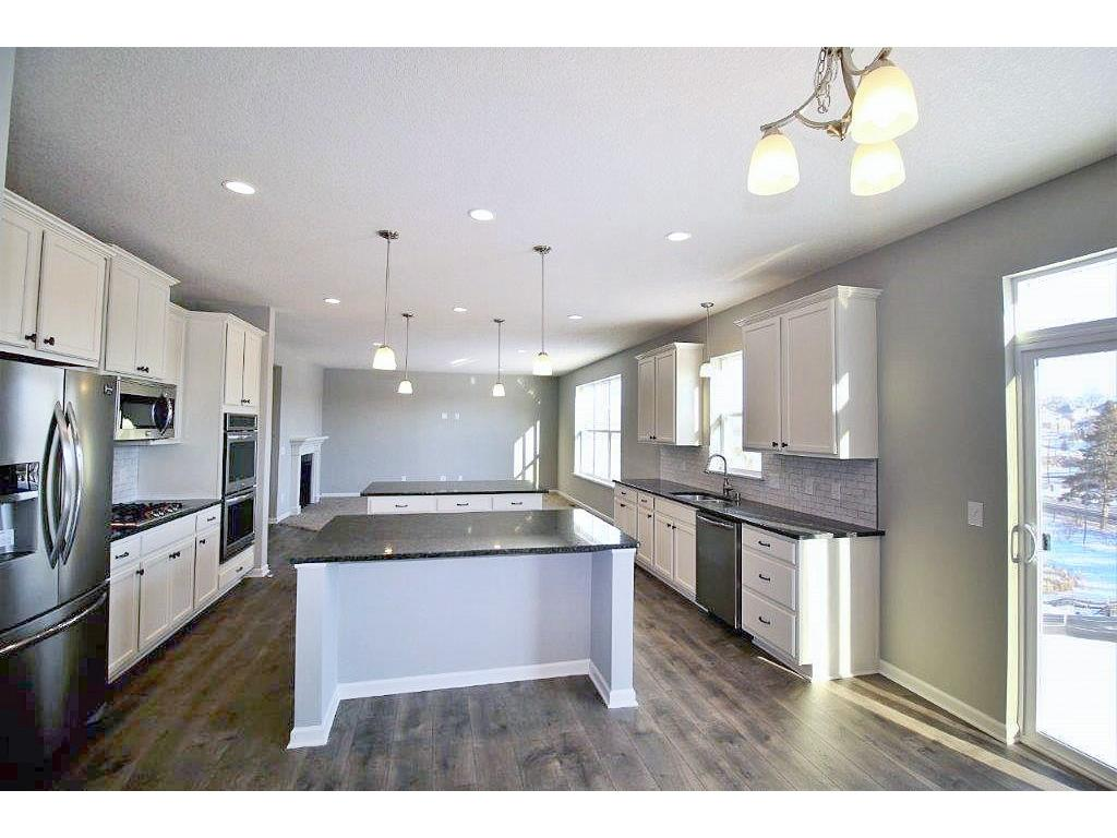Gleaming floors surround the generous island countertops and huge dinette. Walk-in pantry and the Signature option-stainless steel top and bottom ovens, plus a vented hood for the cook. An Elegant and special kitchen to showcase!