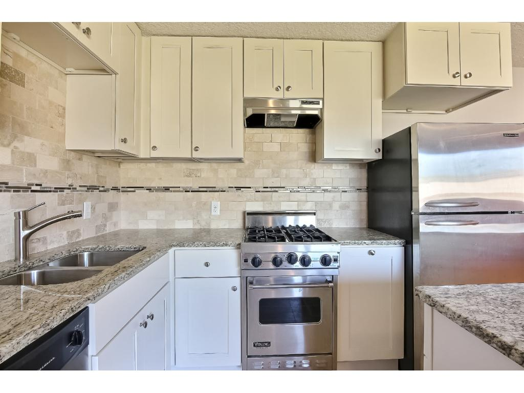 Totally remodeled kitchen with new white enamel cabinets, granite counters and SS appliances.