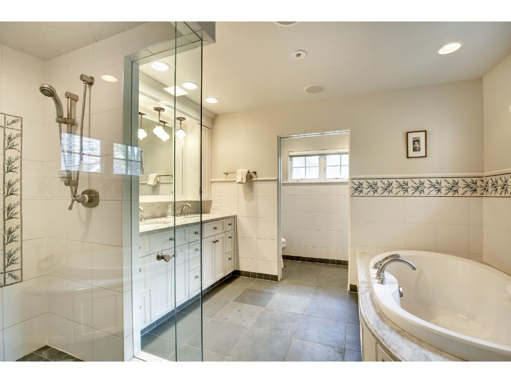 Owner's bath features double vanity, walk-in shower, whirlpool bath and separate WC.