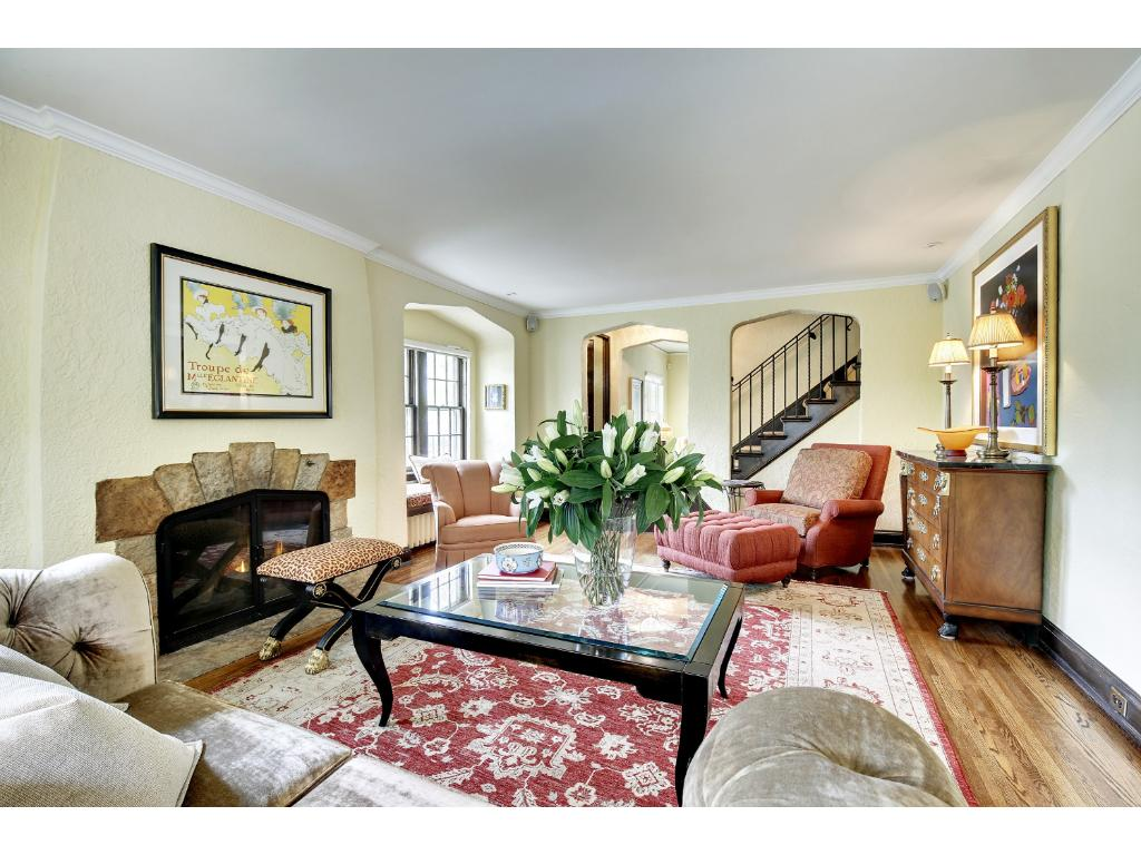 Grand living room features a stone fireplace, crown moulding, wrought iron staircase original to the home's construction.