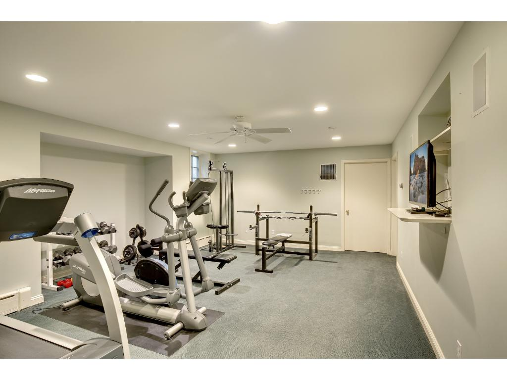 The large home gym has space for machines and free weights and leads to two off-season finished storage rooms.