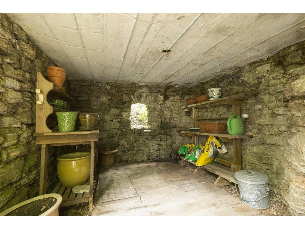 The charming grotto in the backyard serves as a storage and potting shed.