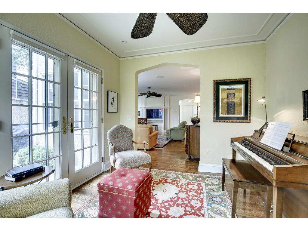 Sunny music room leads to a private side courtyard.