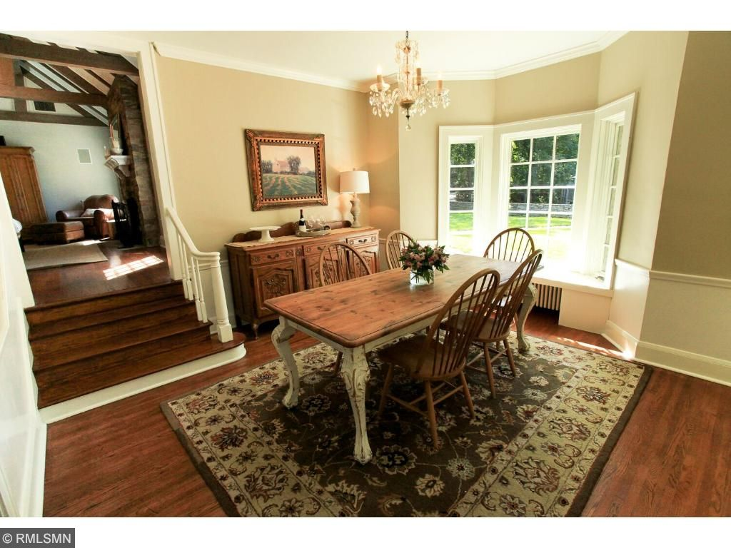 Spacious sunny dining room features large bay window and window seat and extra high ceilings