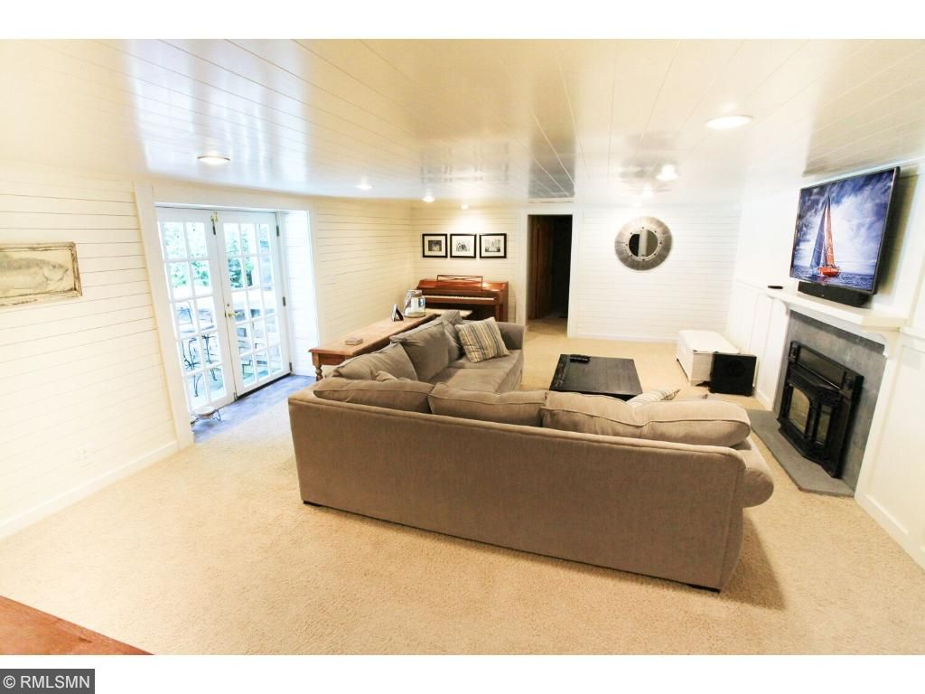 Newly updated lower level family room features ship lap walls and planked ceiling, blue stone fireplace and custom built in bar/serving area for entertaining after a day enjoying the pool