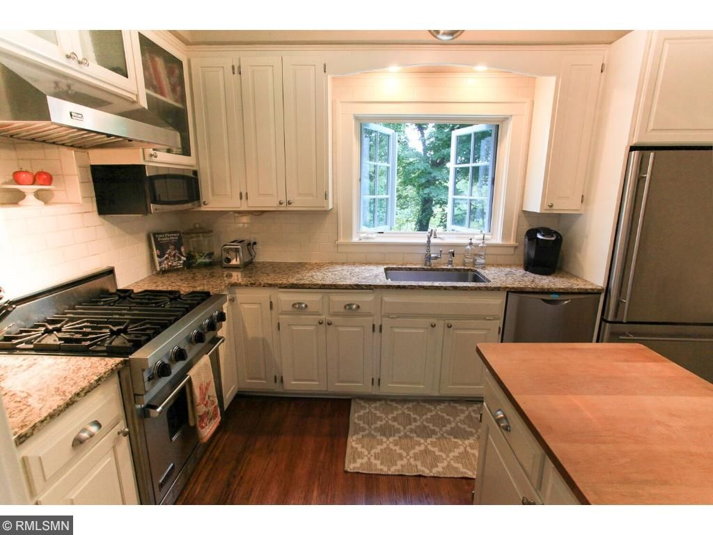Such a pleasant room with stainless steel appliances, Viking stove, granite counters, enameled cabinetry and an awesome european style window over looking the beautiful nature-filled back yard and pool area