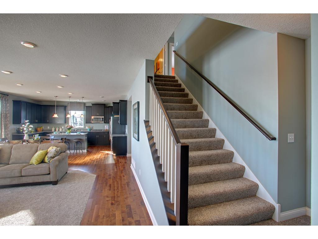 One of the home's most noticeable features, this extra wide staircase leads up to a 2nd story that is home to 4 bedrooms, 2 bathrooms, a laundry room and an extra living room every growing family is looking for. (Photo of model, finishes will vary)