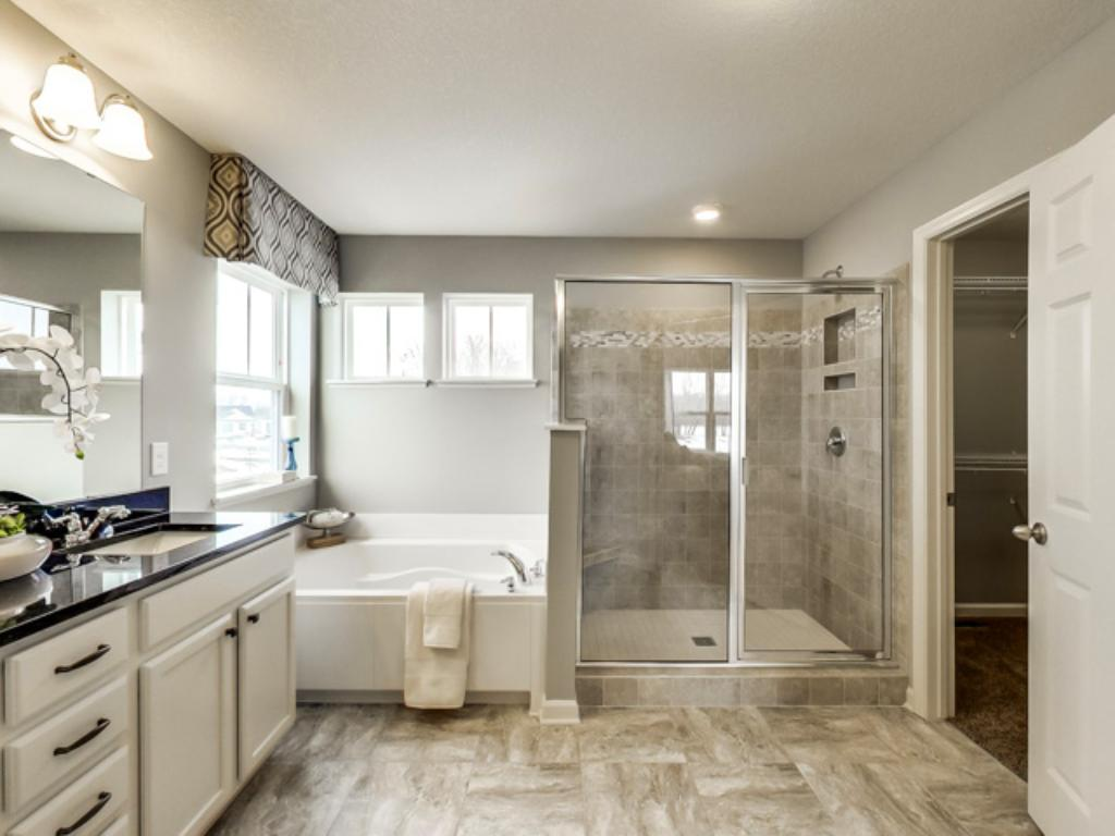 An extension of the owner's suite, this private and spacious bathroom is home to a double-vanity, a separate shower and tub, a private water closet, plus those TWO walk-in closets. (Photo of model, finishes will vary)