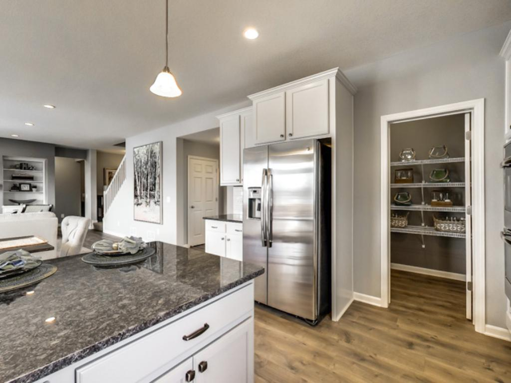 The kitchen leaves plenty of space for the chef to maneuver, and is also home to a 9-foot deep pantry closet for all of your goods. (Photo of model, finishes will vary)