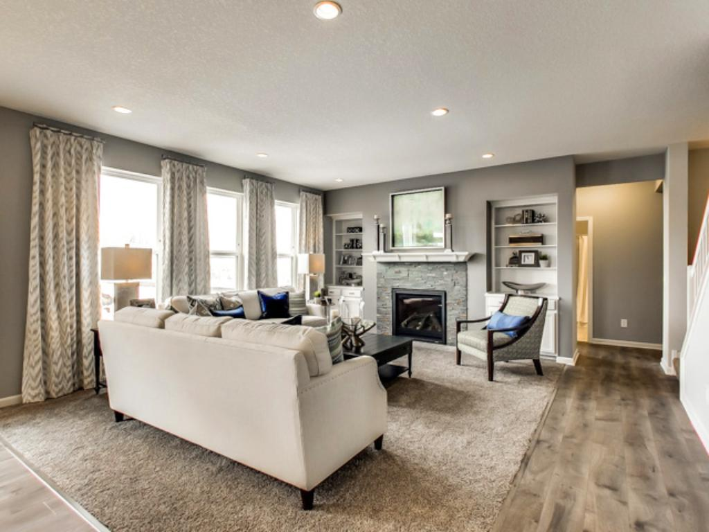 Soaring windows allow natural light to flow throughout the main level, including this nicely sized family room, which also features a natural gas fireplace.
