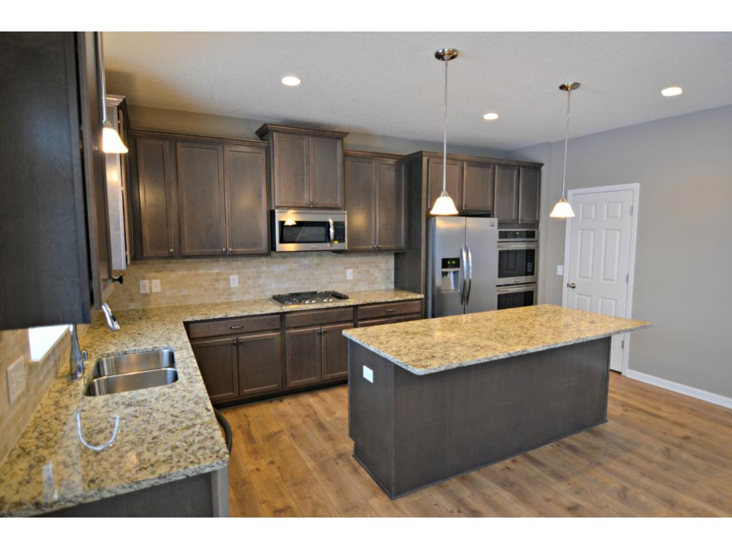Open and naturally bright, the home's kitchen is one to be desired and will feature a full SS appliance package including 4-burner gas cooktop, double ovens, refrigerator, microwave with vent and dishwasher. Photo of model, finishes will vary.