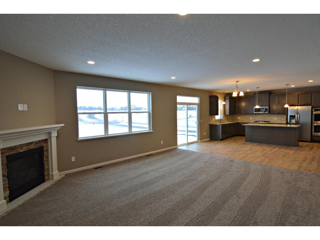 The main level family room measures 18x17 and comes furnished with a corner gas fireplace and is flooded in light from all the large windows. Photo of model, finishes will vary.