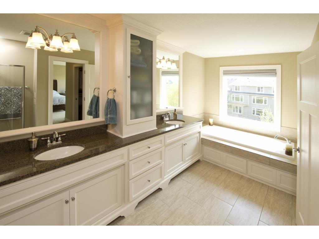 The private master bathroom features a double vanity, large soaking tub, and a walk-in shower.