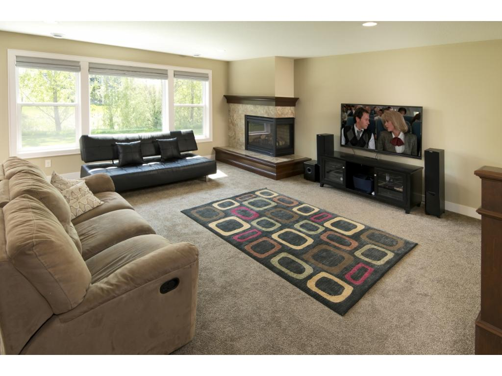 The lower level family room has an abundance of natural light and a two-sided corner fireplace.