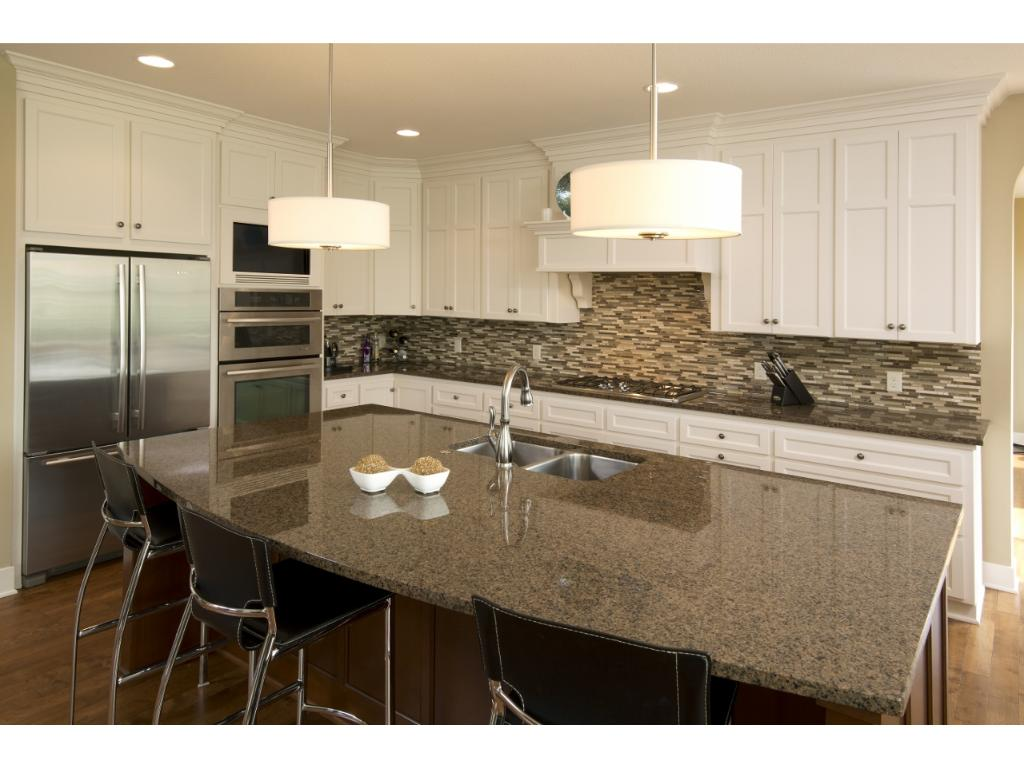 The gourmet kitchen is highlighted by a double oven, beautiful cabinetry, and granite counter tops.