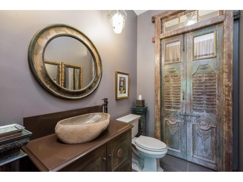 Polished carved stone sink and custom closet doors all in the main floor powder room.