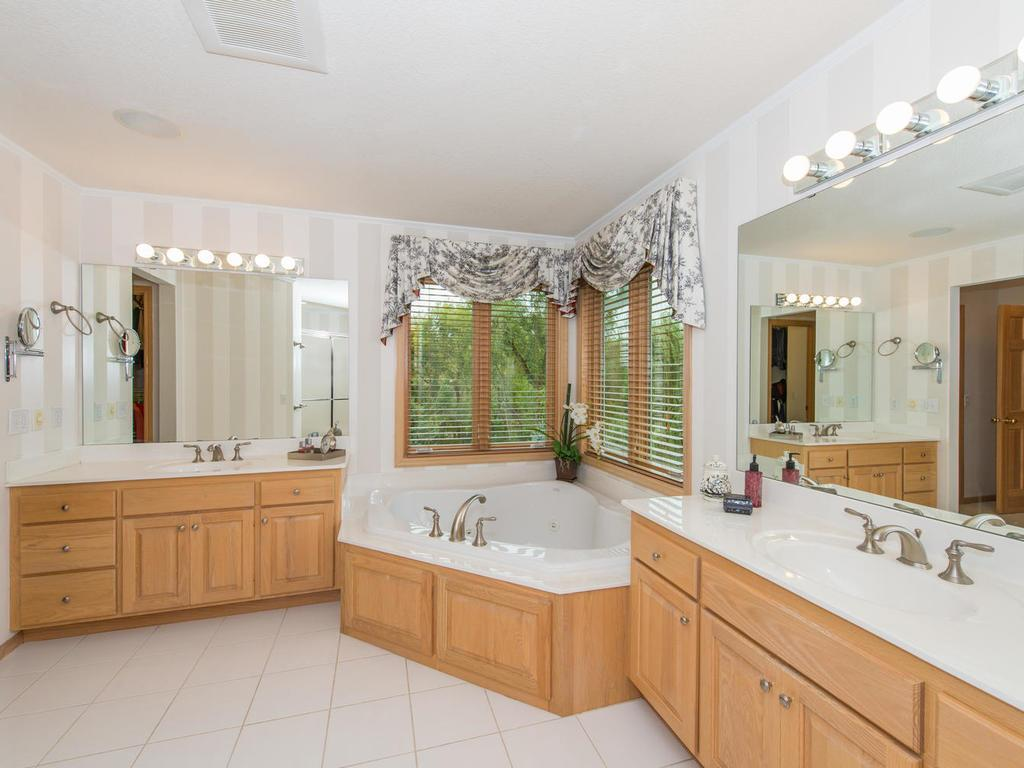 The Master Bath features his & hers vanities, a large corner whirlpool tub, separate walk-in shower, and a toilet room.
