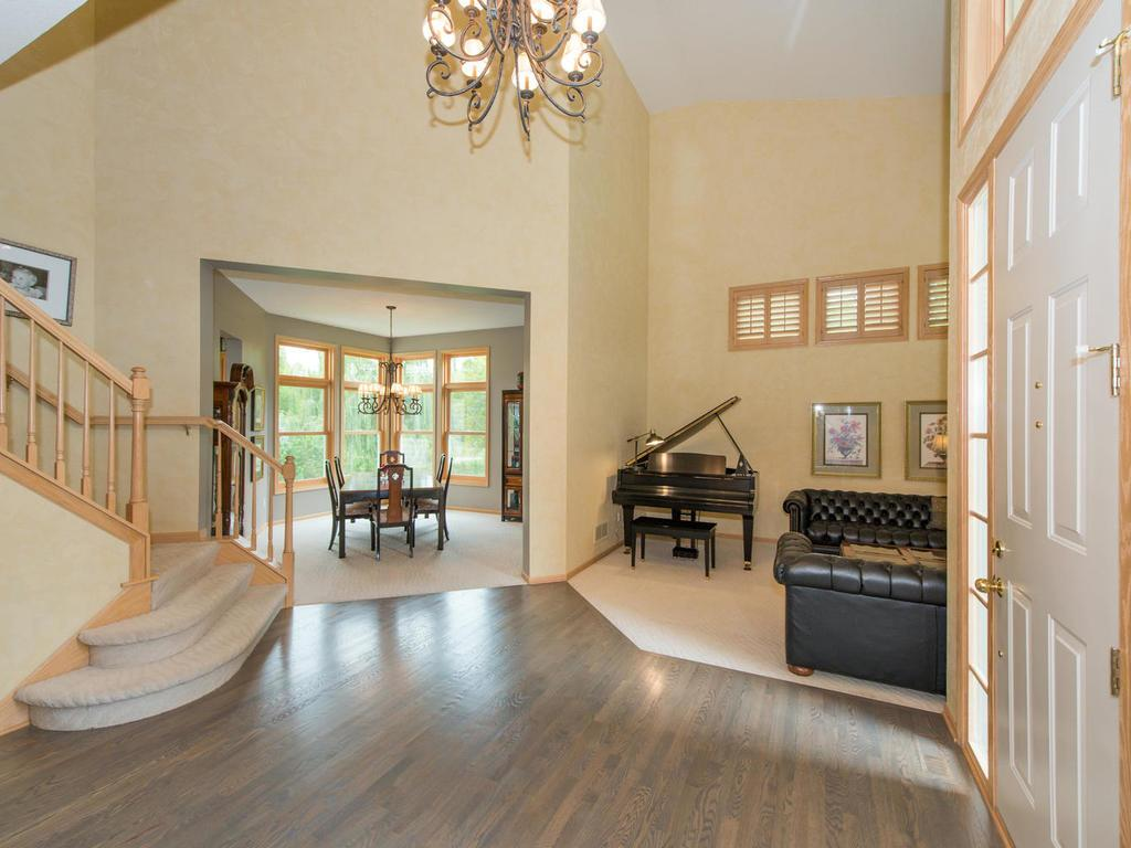 The Foyer and Living Room features a 20' ceiling, Venetian plaster, plantation shutters, and lead into the Formal Dining Room. Off the Foyer, you can also access the 13x11 Office through the French doors.