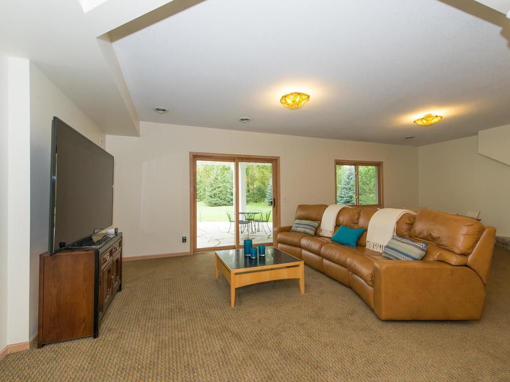 Lower level Family Room measures 25x15, features a 3 sided fireplace, a designated Bar Area with ceramic tile, and walks-out to the beautiful flagstone Patio and Backyard.