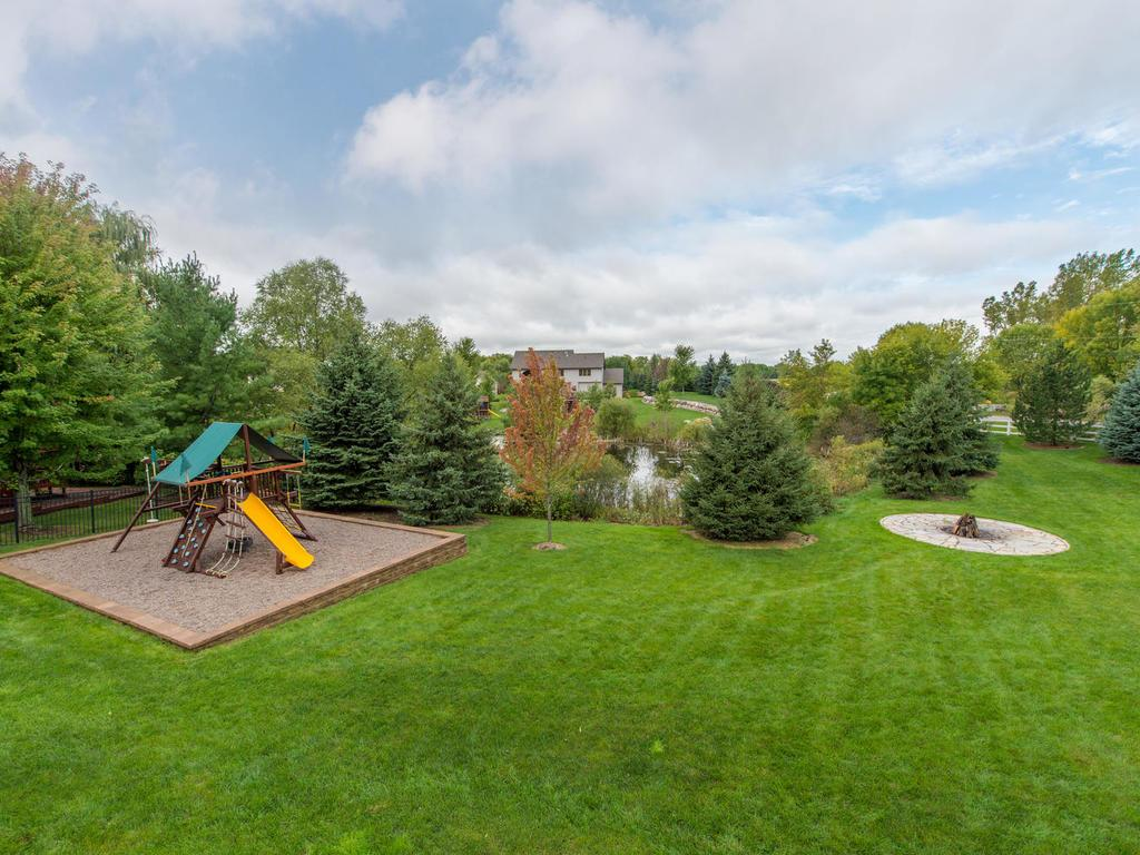 View of the playset, fire-pit area, and the pond from the Deck.