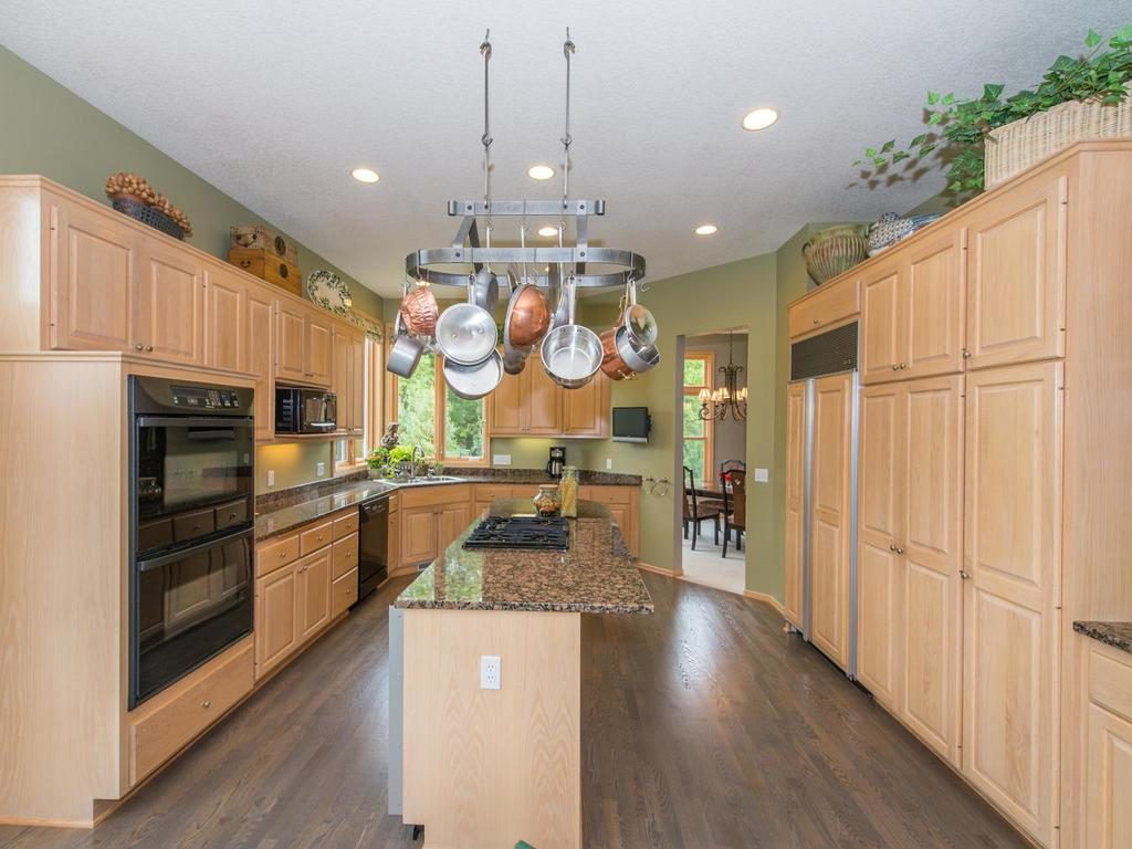 The newly refinished white oak floors continue into the Kitchen with its granite countertops, high-end appliances, and plenty of custom white oak cabinetry with whitewash finish. Large center island features a cooktop and breakfast bar seating area.