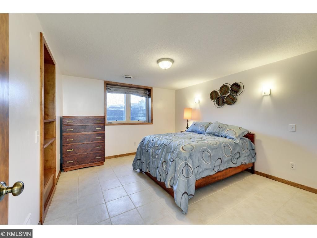 Spacious lower level bedroom with tile floors and egress window