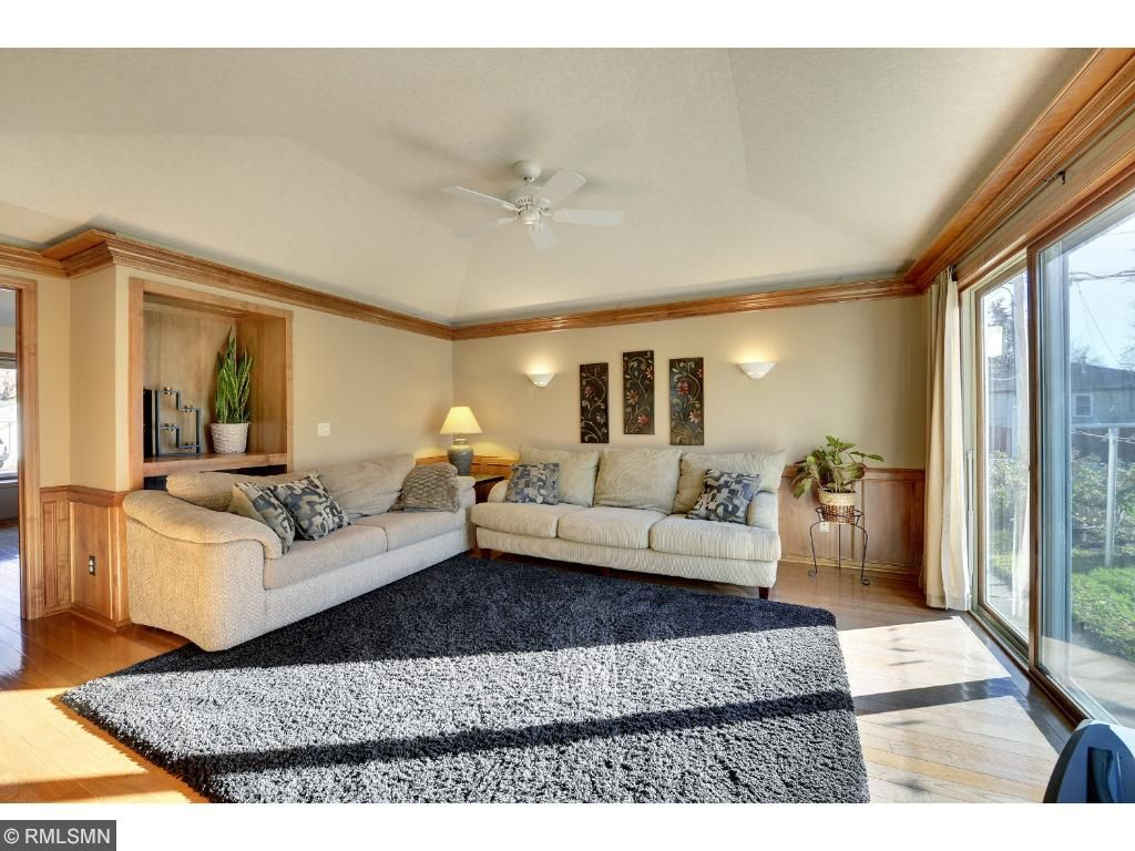 Main level living room featuring vaulted ceilings, abundant natural light and hardwood floors.