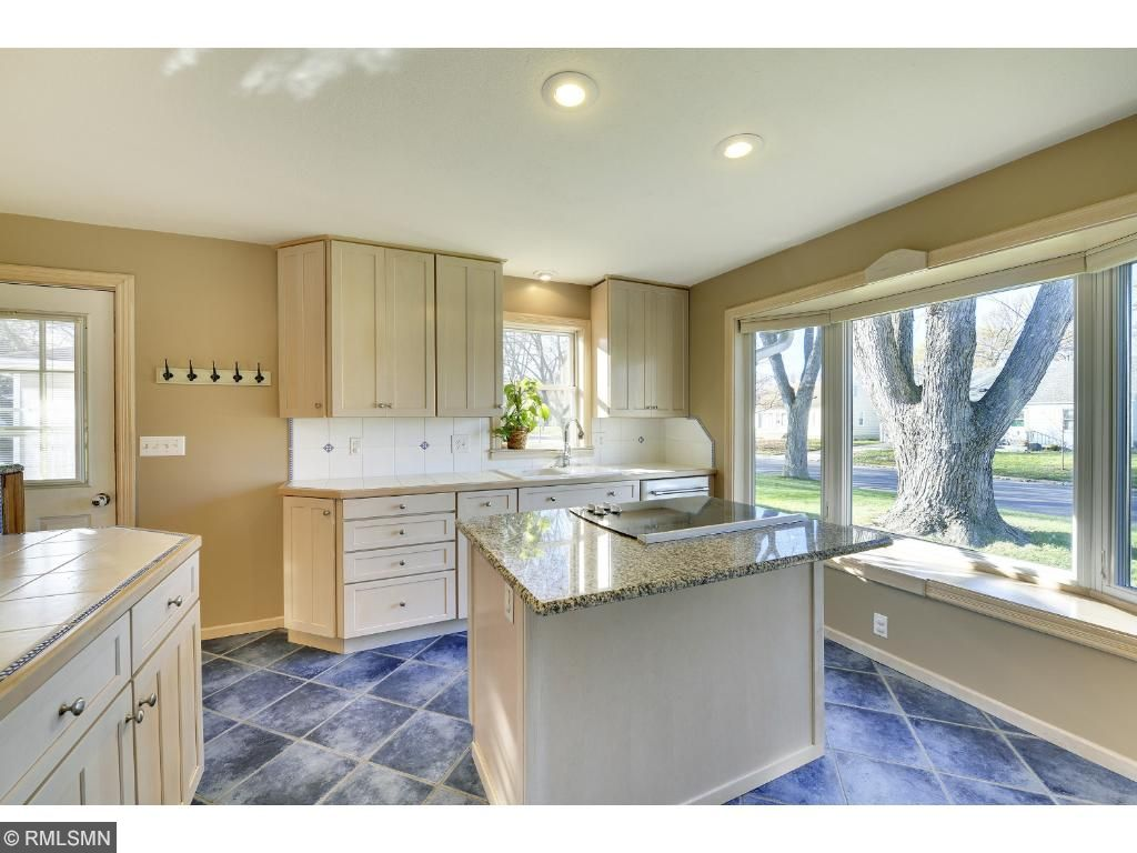 Kitchen featuring center island, double wall oven, cooktop, bay window,  abundant natural light and more