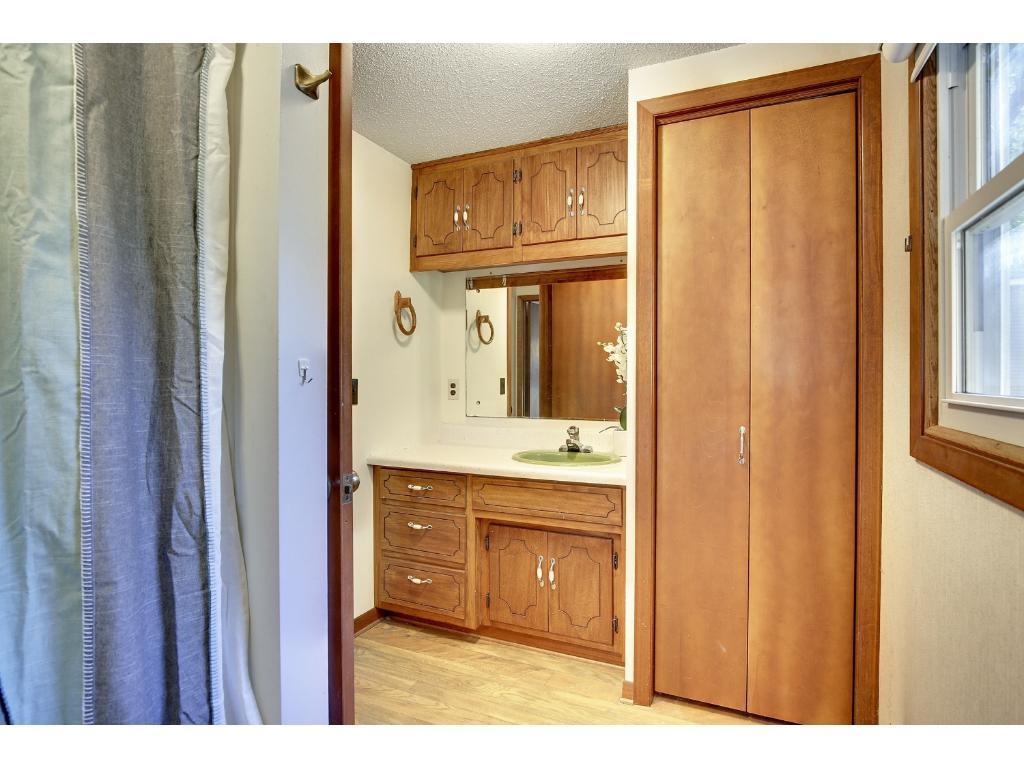 Full bathroom with storage closet near bedrooms.