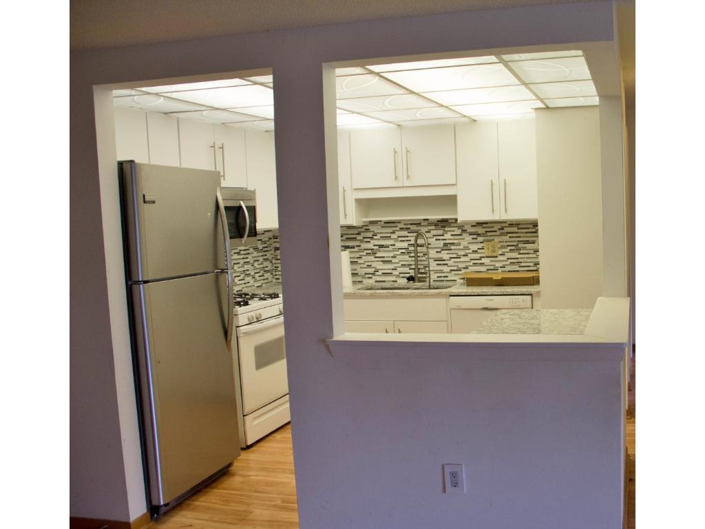 Quartz countertops and tile backsplash. Cabinets are fairly new.