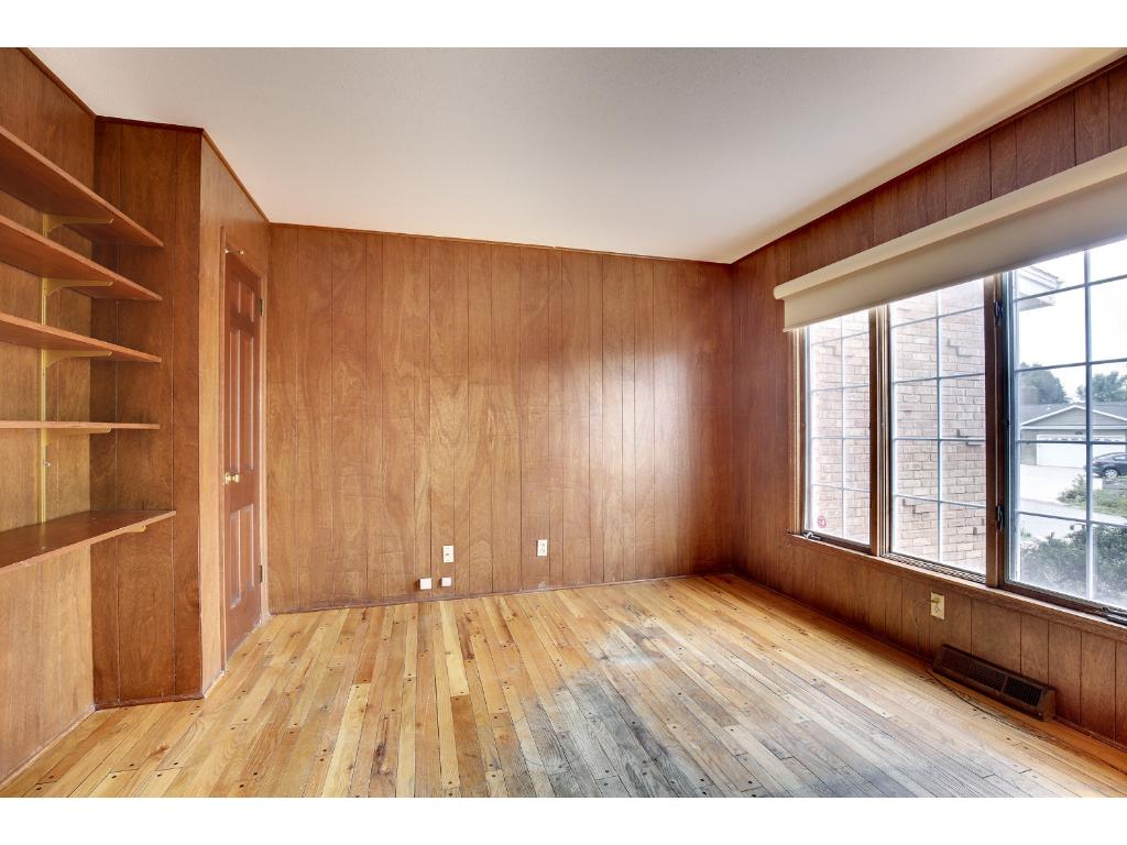 The main floor den features wood floors, paneled walls and has a south facing window for tons of light