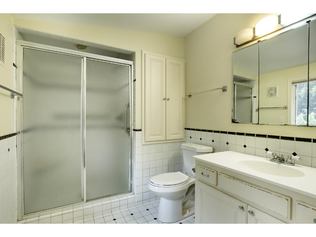 The ceramic tiled master bath features a single vanity with storage underneath and a large walk-in shower