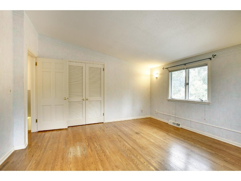 This room is accentuated with a vaulted ceiling, white woodwork and beautiful hardwood floors