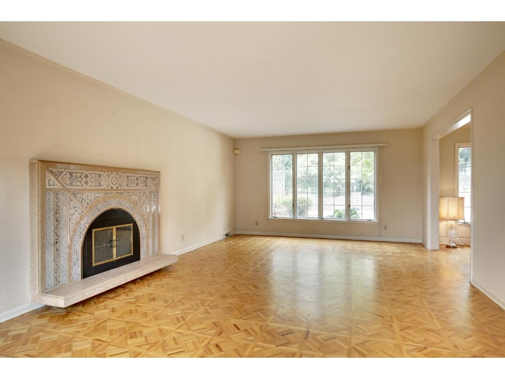 The living room measures 26x14 and is accentuated with parquet flooring and a wood burning fireplace