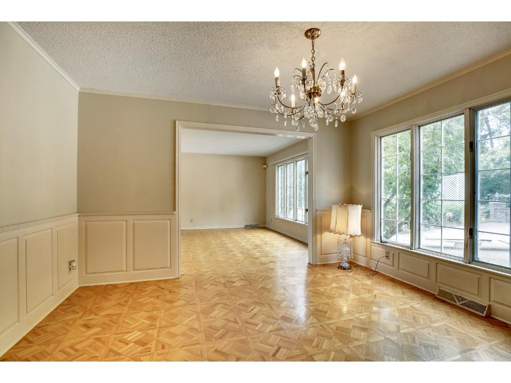 The formal dining room features parquet flooring and has a large window overlooking the backyard