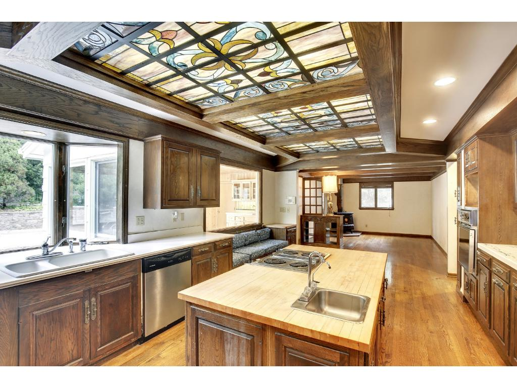 The kitchen features stainless steel appliances and a boxed beamed ceiling accentuated with stained glass