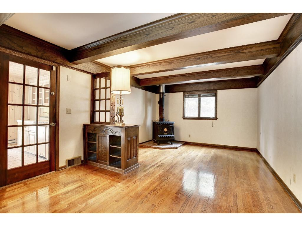 The main floor family room has hardwood floors with boxed beams on the ceiling and a wood burning stove