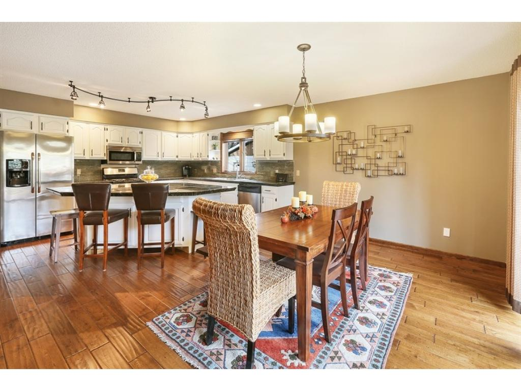Upper level hall features hand-scraped wood floors and offers an opening into the kitchen.