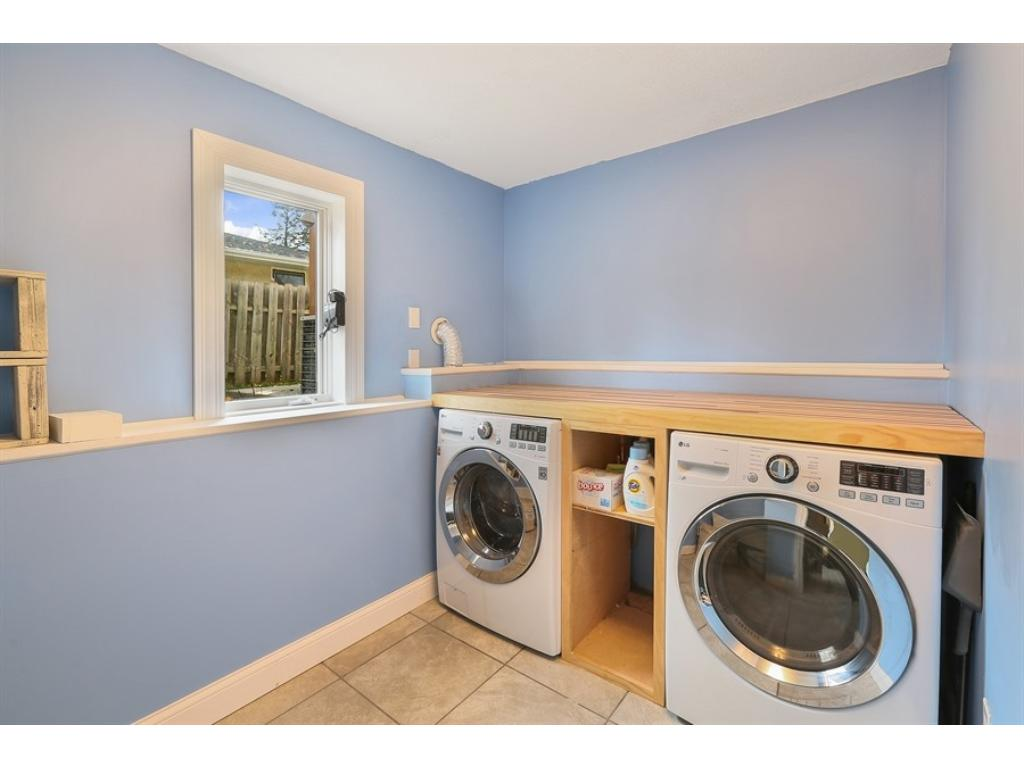 Spacious lower level half bath with ceramic tile, marble vanity, storage closet, & more!