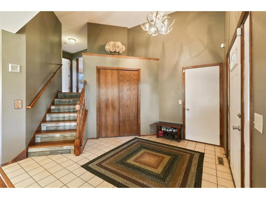 Dramatic foyer with vaulted ceiling, chandelier, large display ledge, coat closet, ceramic tile floors, and more!
