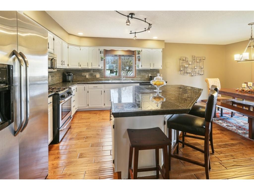 Superb chef's kitchen with oversized center island, elegant granite countertops, stacked slate backsplash, newer stainless appliances, & more!