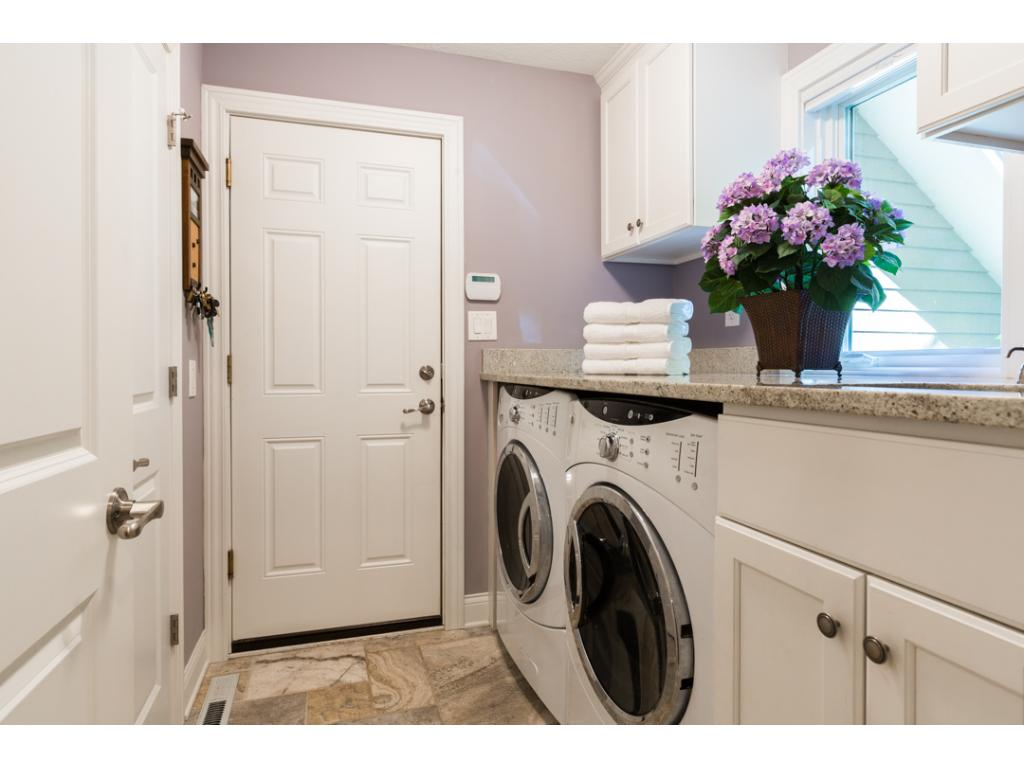 Main level laundry includes natural stone tile floor, large pantry closet & extra large capacity GE front loading washer & dryer. Provides garage access + mudroom.