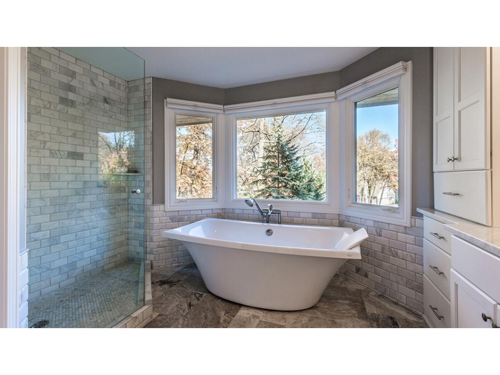 Luxurious private Master BA is beautifully appointed w/natural marble counter & dual sinks, Travertine floor, walk-in shower w/marble subway tile & Kohler free-standing soaking tub w/large bay window above. A separate commode room for added privacy.