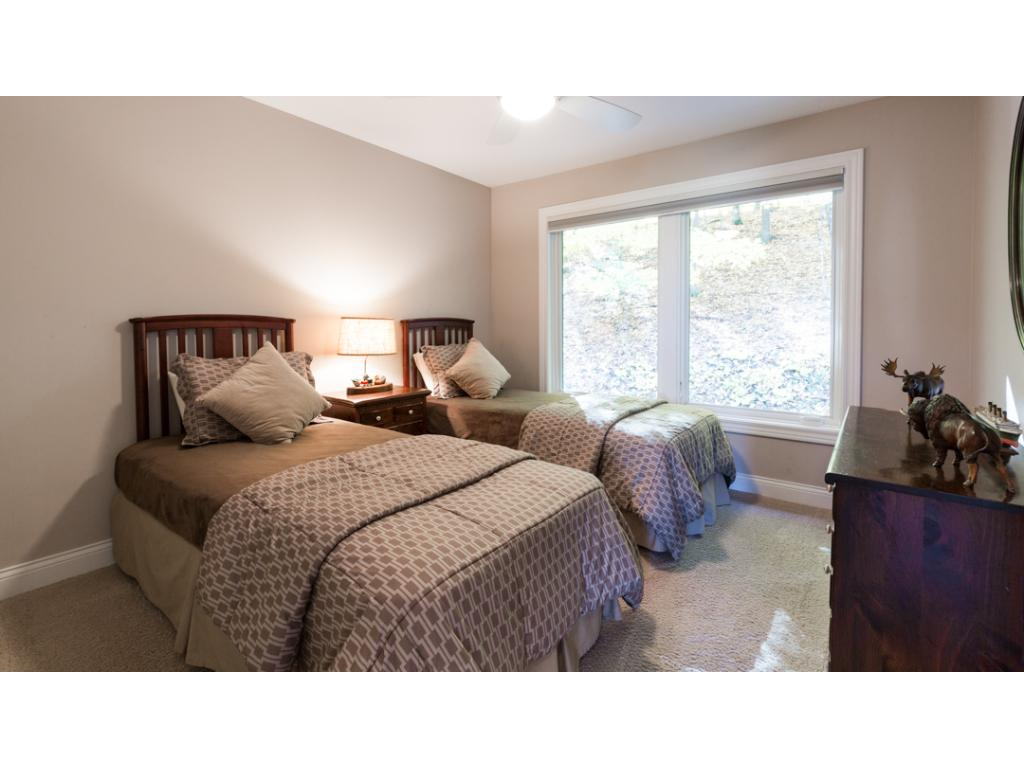 View of 1 of 3 junior bedrooms on the upper level. All offer large closets w/ French doors & custom shelving which can also be found thru-out whole home.